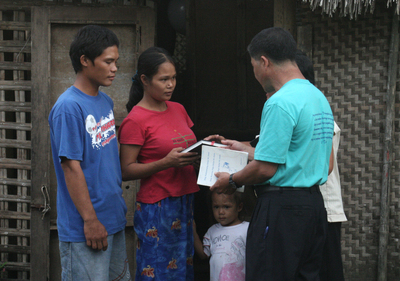 A pastor visting a famliy at home and leading them in a Bible study.